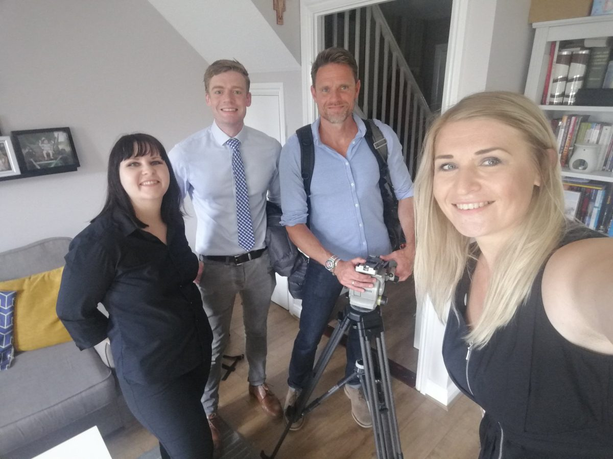 Gosia in a living room during filming, with ITV News mentor, Nick Smith, a camera man and an interviewee.